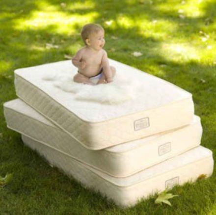 baby on stack of mattresses